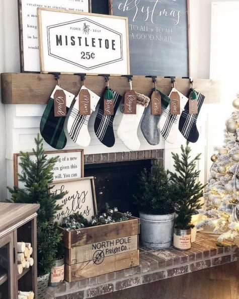 a farmhouse living room with plaid stockings, a crate with evergreens, mini Christmas trees and a neutral Christmas tree