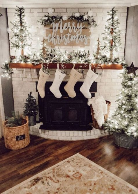 a neutral farmhouse living room with lights, mini Christmas trees, pinecones, white stockings and a sign