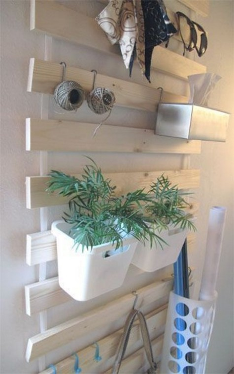 a whitewashed IKEA Lattenrost hack with hooks and planters attached to it for an entryway