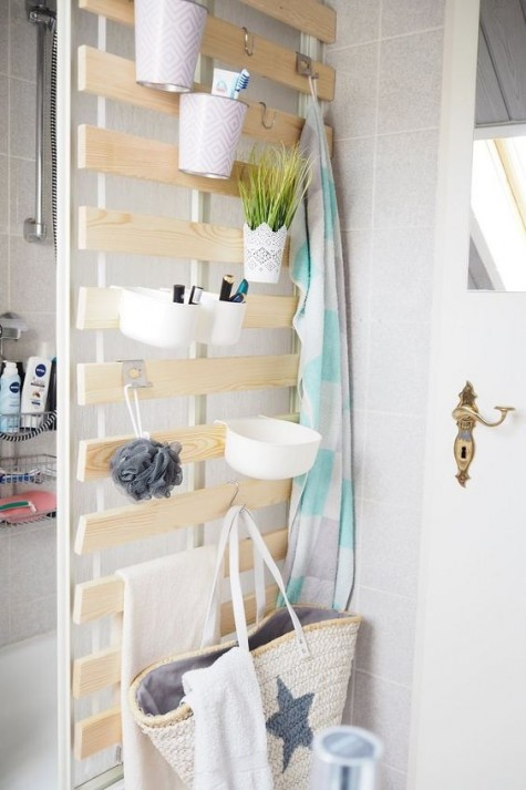 an IKEA Lattenrost hack for a bathroom, with hooks and containers for holding all kinds of stuff