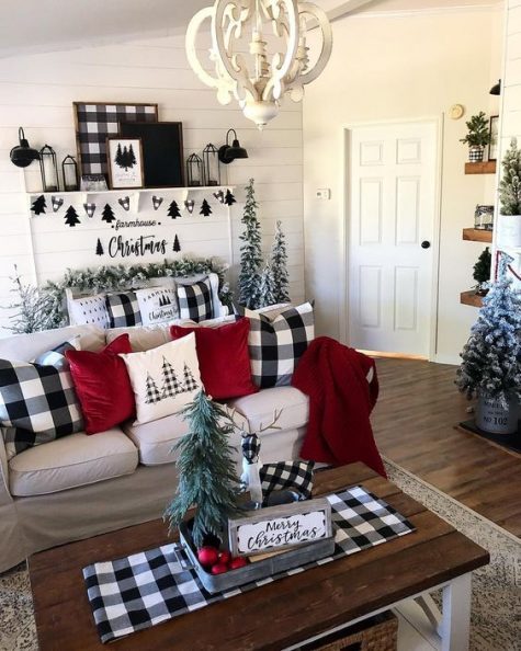 farmhouse Christmas decor with red and buffalo check pillows, snowy Christmas trees and garlands, a black tree bunting and artworks that match
