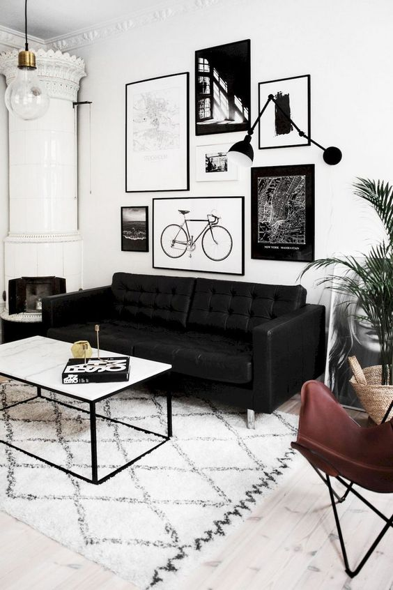 a bold black and white living room with a graphic gallery wall, a pritned rug and a tile stove in the corner