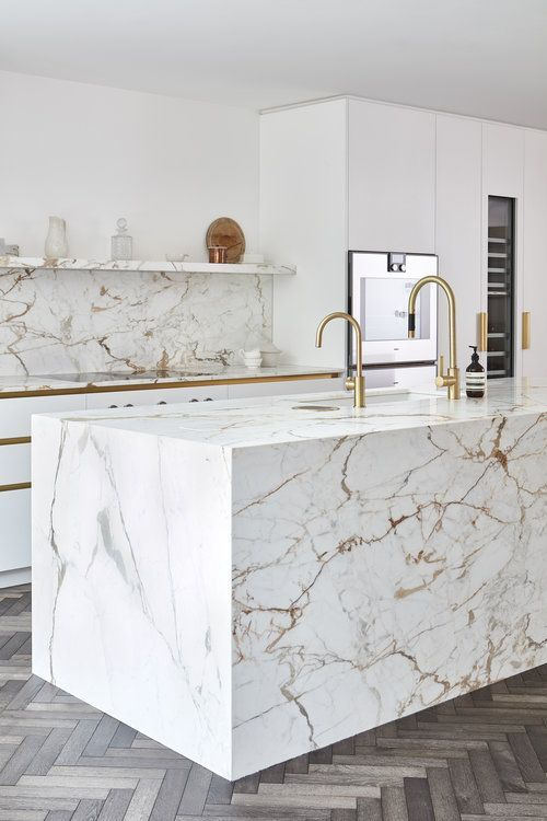 a chic white kitchen done with strongly veined marble - on the backsplash, countertops and kitchen island