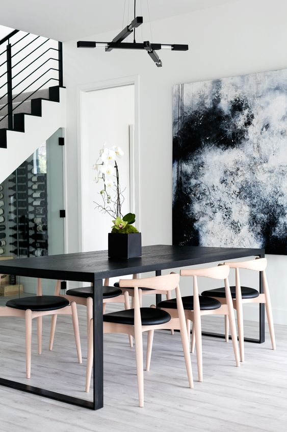a chic contemporary dining room with a black table and a fantastic watercolor artwork on the wall