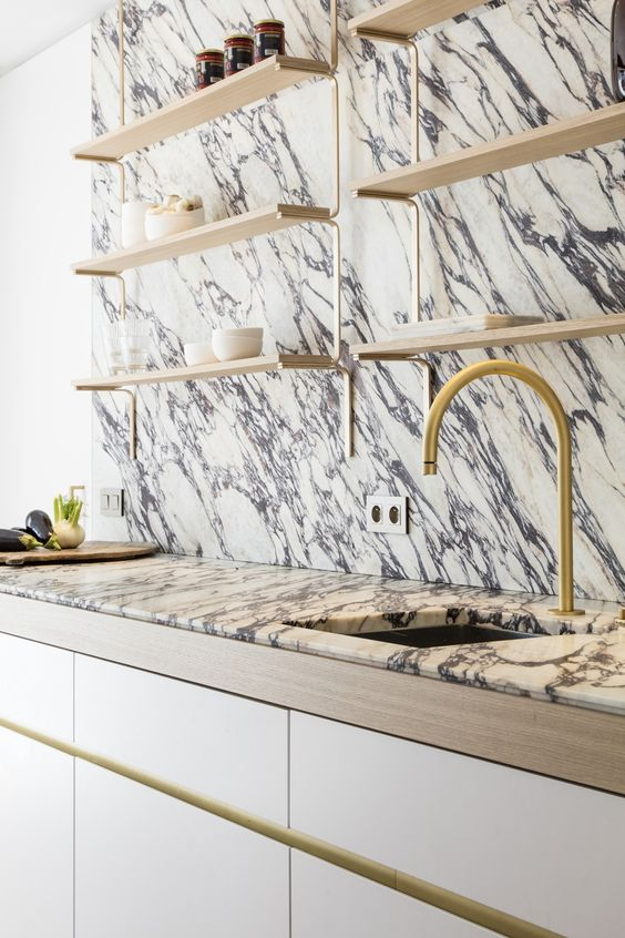 a dramatic kitchen look with veined marble on the wall and countertops plus gold fixtures