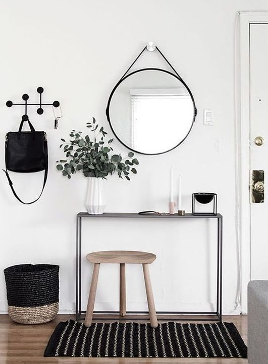 a chic Nordic entryway with a printed rug, a black console, some touches of natural wood