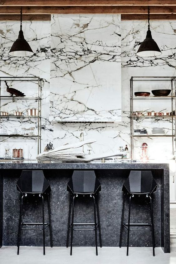 a monochromatic kitchen made bolder with strongly veined marble that covers the whole wall
