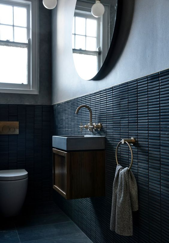 a moody contemporary bathroom with long and sleek tiles, a floating vanity and a round mirror