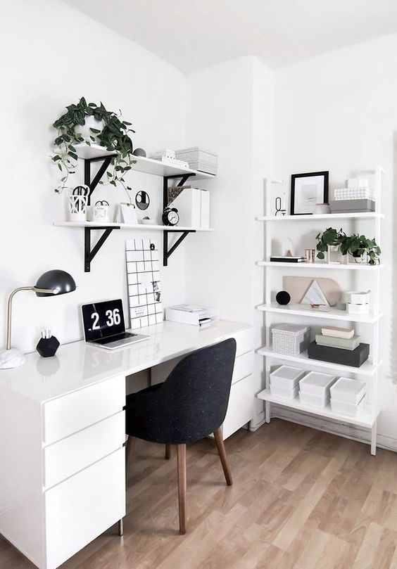 a comfortable Nordic working space with lots of shelving units, a comfy desk and a cozy black chair