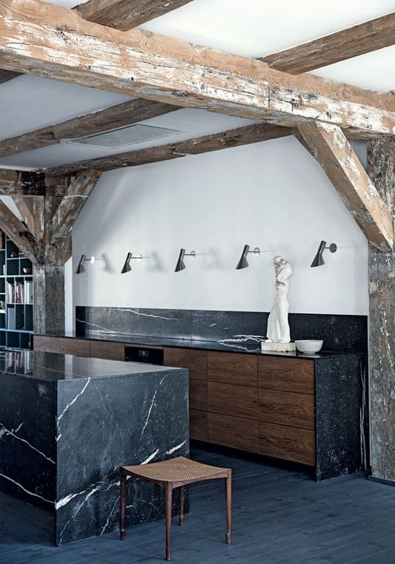 a moody kitchen with strongly veined marble in black and sleek wooden cabinetry for a wow look