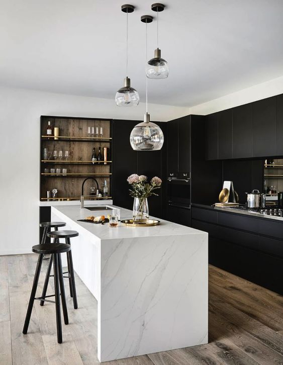 a gorgeous minimalist kitchen with sleek black cabinets, a white marble kitchen island and a wooden shelving unit