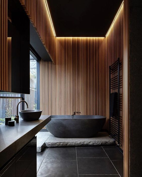 a moody zen bathroom done with wooden slabs and stone in dark shades, with built-in lights