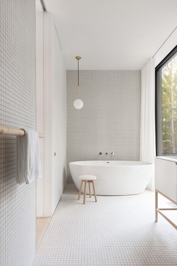 a minimalist neutrla bathroom with mini tiles for texture, a free-standing tub and a glazed wall for a view