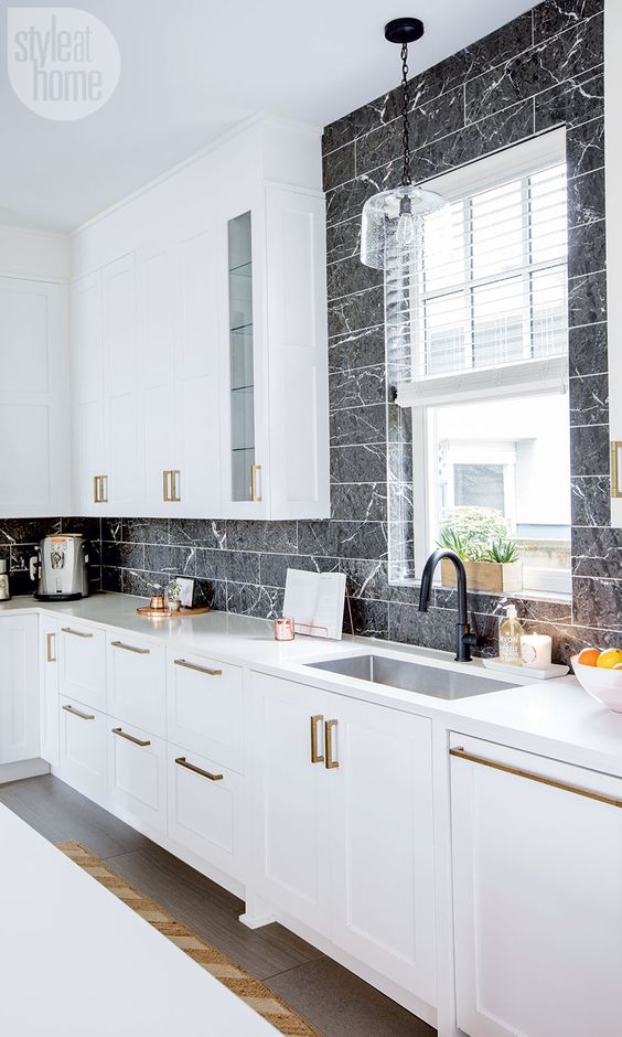an elegant white kitchen with black marble veined tiles that make the cabinetry stand out a lot
