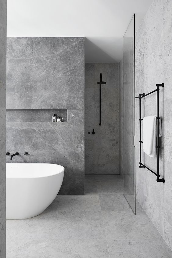 a minimalist bathing space done with grey marble tiles and matte black fixtures for a chic look
