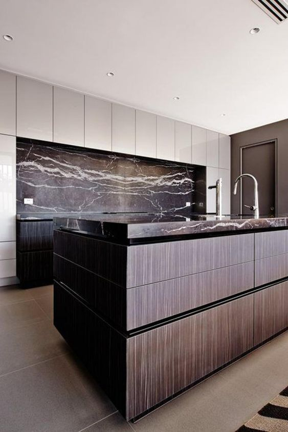 a moody kitchen with black veined marble that covers the backsplash and countertops for eye-catchiness