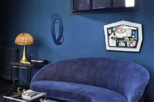09 a classic blue room with a whimsy navy sofa, some artworks and side tables
