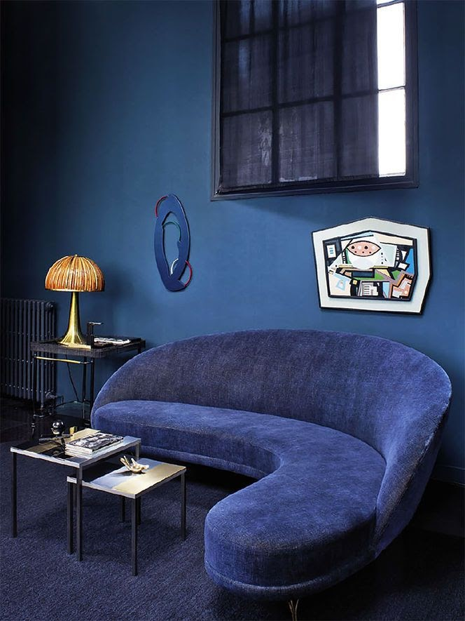 a classic blue room with a whimsy navy sofa, some artworks and side tables