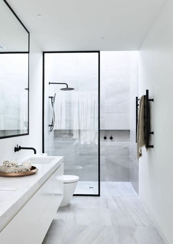 a neutral minimalist bathroom done with grey marble tiles, stone countertops and black touches for drama
