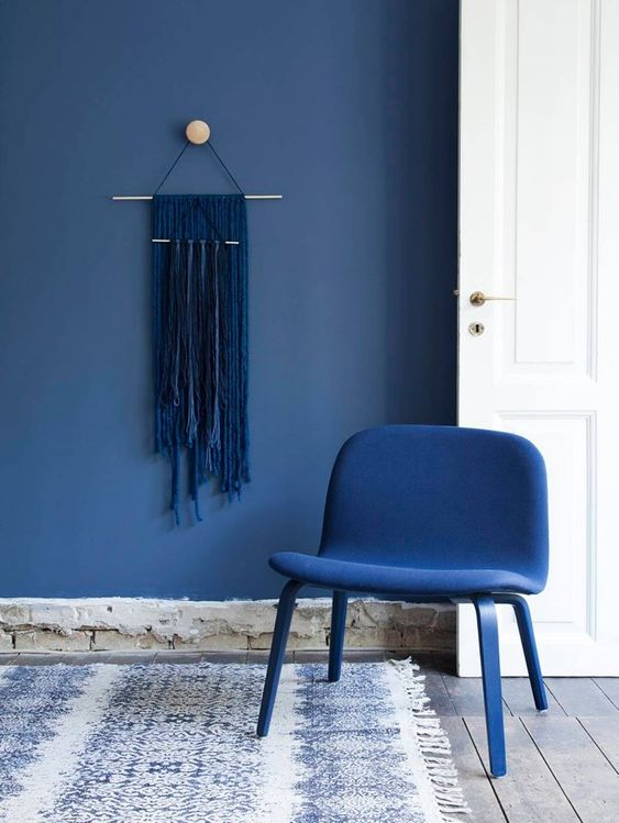 a classic blue accent wall and a matching chair plus a navy yarn hanging on the wall - the whole space filled with blues