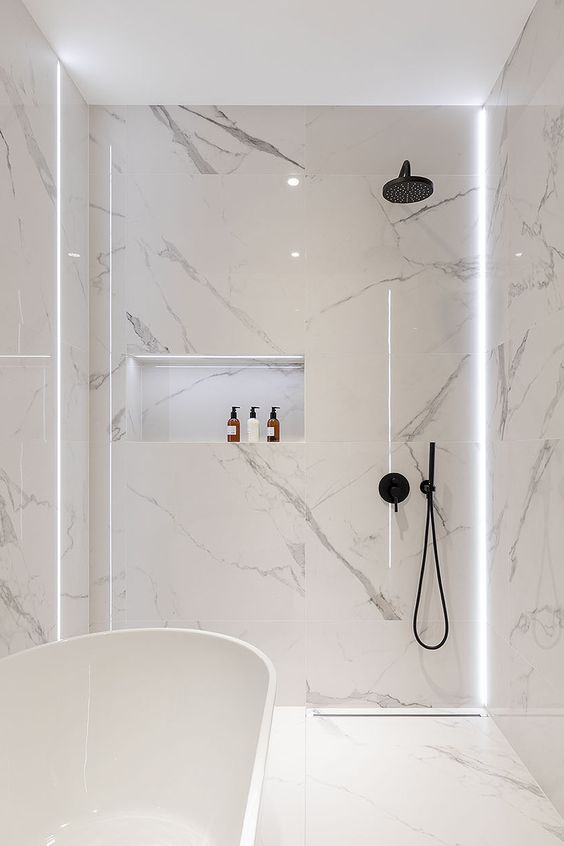 a minimalist white bathroom with white marble tiles, a free-standing tub and matte black fixtures