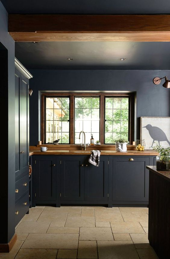 a moody navy kitchen with wooden countertops that warm up and soften the space a lot