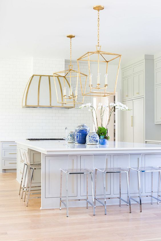 large brass lamps and a hood with a touch of brass are bolder than stainless steel chairs