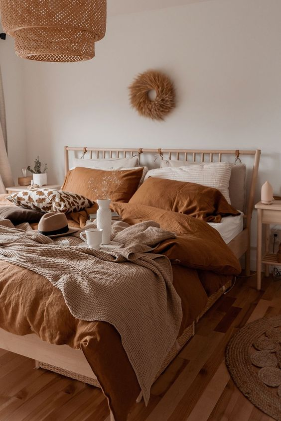 a cozy and welcoming earthy tone bedroom done in greys, beige, tan and rust plus some neutrals