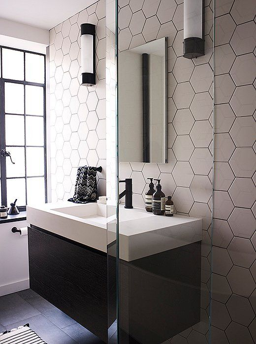 neutral hexagon tiles make the wall stand out and they are accented with blakc grout additionally