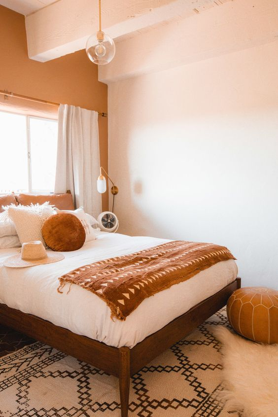 a chic and welcoming bedroom done with touches of rust and orange and much neutral
