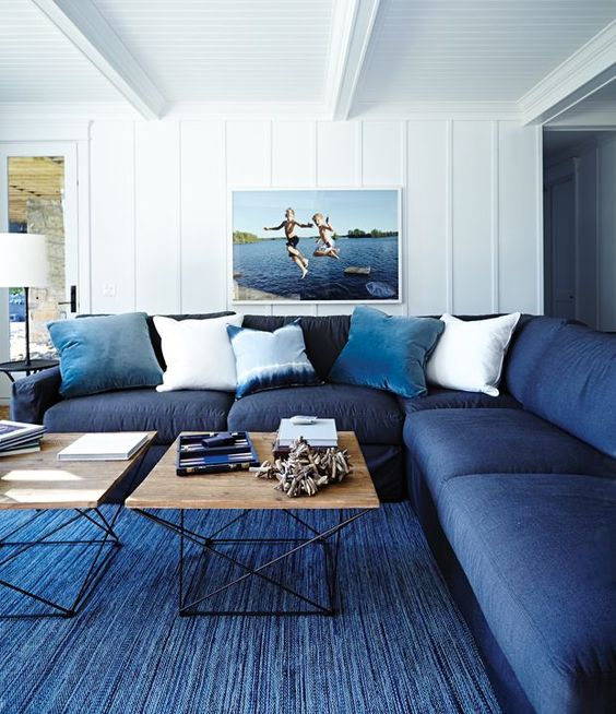 a classic blue rug and a navy sofa plus light blue pillows make the space feel beachy