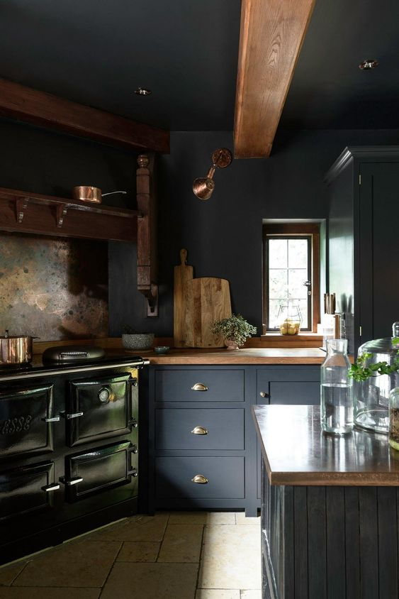 a moody navy kitchen with wooden countertops and beams, a vintage hearth and some chic copper touches