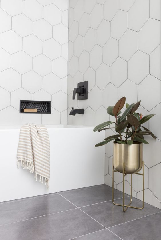 oversized white hexagon tiles accented with black grout for a chic and bold bathroom look with a modern feel