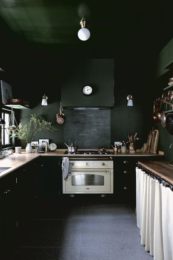 a black kitchen with chic vintage touches and wooden countertops plus white elements to refresh the space