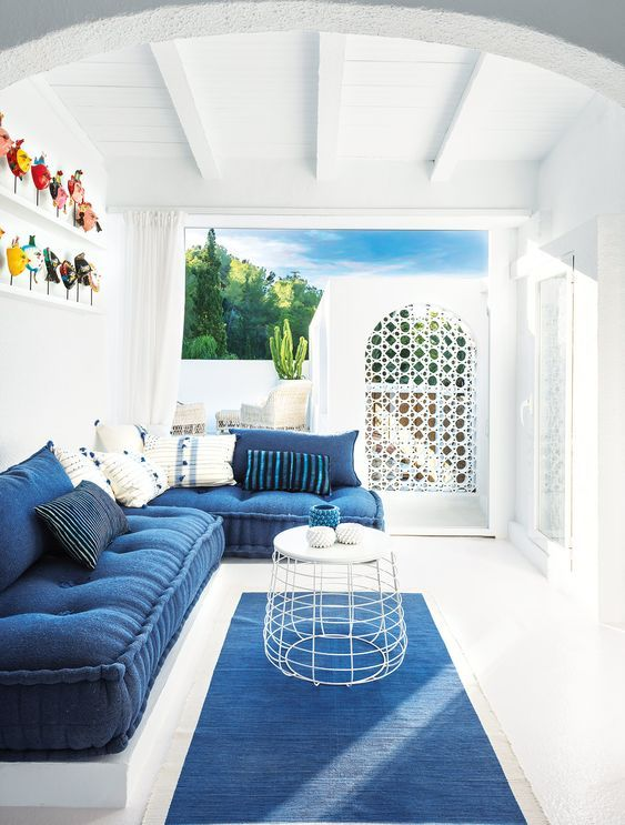 a classic blue rug, a matching L shaped sofa and a painting on the wall make the space feel coastal and beachy