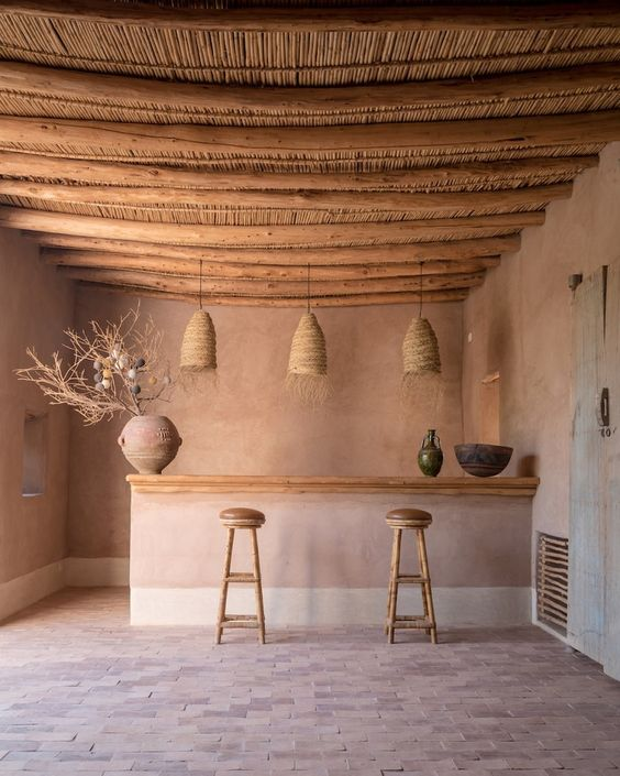 a unique earthy tone kitchen with a wooden ceiling, wicker lamps, wooden stools and terracotta vases