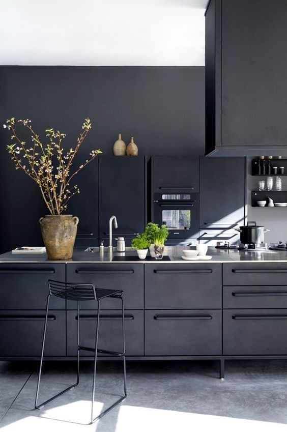 a contemporary moody kitchen with black cabinetry of metal and white countertops plus a metal stool
