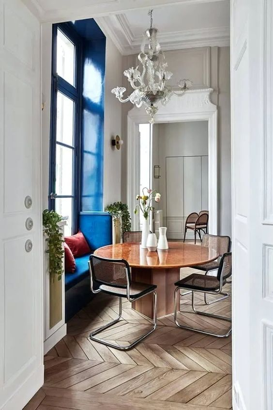 a cozy window seat accented with classic blue is a chic and refined idea to add a touch of color