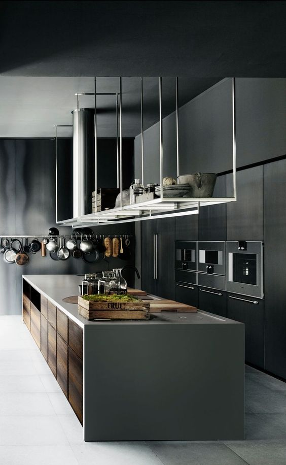 a moody mini,alist kitchen done in the shades of grey, with a large kitchen island and overhead shelves