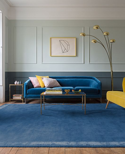 a single classic blue sofa and a muted blue rug that echoes make the space colorful and trendy