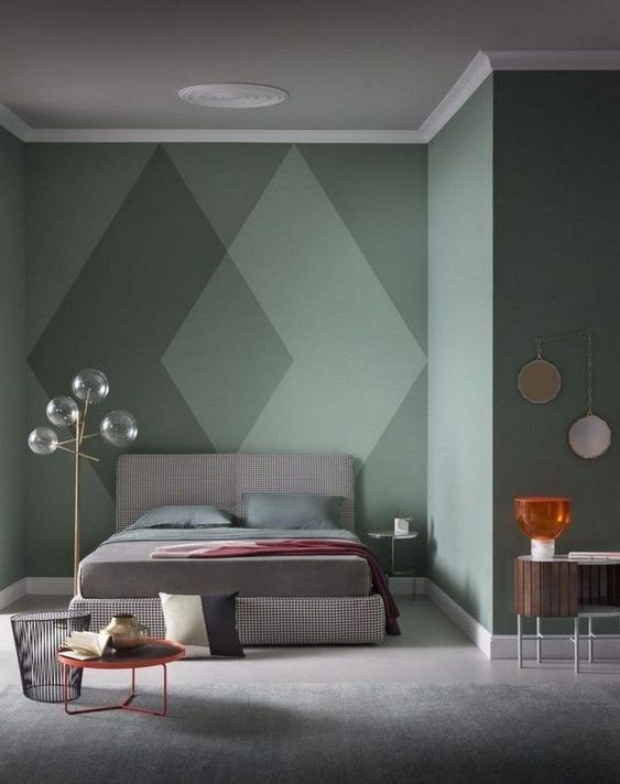 a green statement wall with a cool geometric design that makes the space look catchy and bold