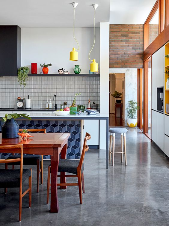 a quirky kitchen with bright yellow pendant lamps and blue tiles on the kitchen island