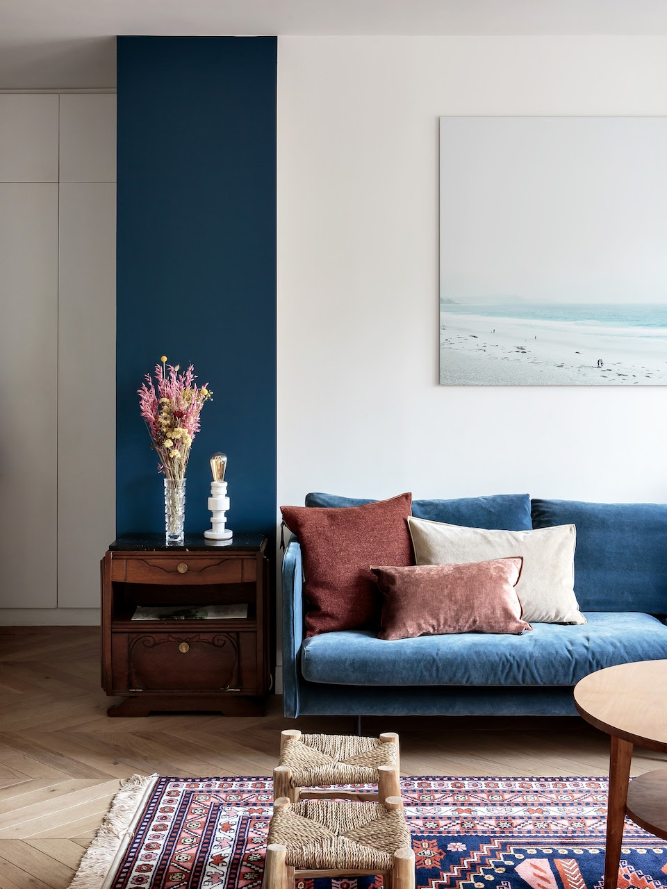 a touch of classic blue brought with a sofa and highlighted with a teal stripe on the wall