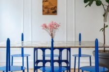 20 a very eye-catchy dining room done with unique metal chairs in classic blue, a catchy chandelier and a table with a classic blue base