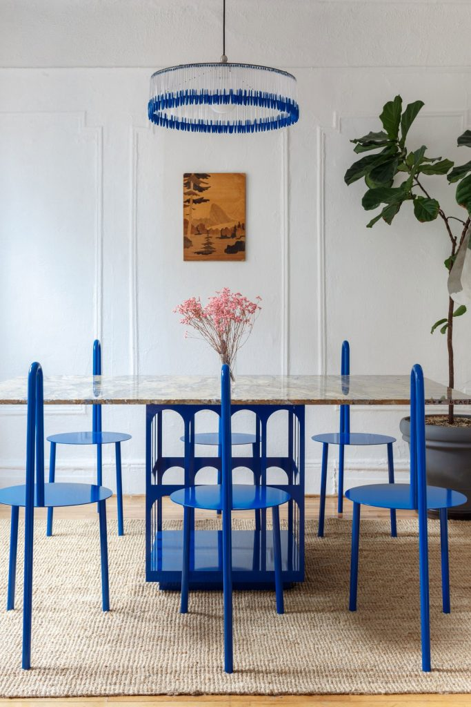 a very eye catchy dining room done with unique metal chairs in classic blue, a catchy chandelier and a table with a classic blue base