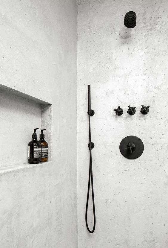 a neutral shower space with a matte black bathroom fixtures looks bold and contrasting