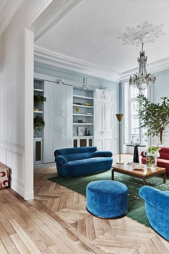 bright classic blue sofas and an ottoman for a trendy colorful touch in the space