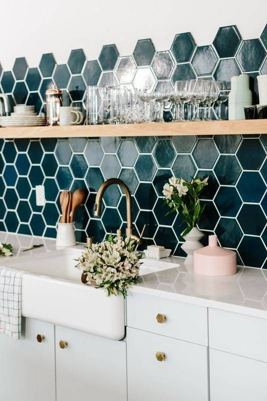 a neutral kitchen with a super bold dark green hexagon tile backsplash that wows