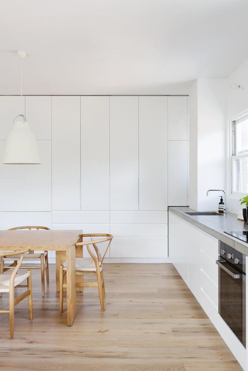 an ultra-minimalist white kitchen with built-in furniture with no handles and concrete countertops