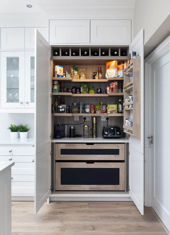 a small yet functional kitchen larger with drawers, shelves and wine storage plus lights